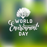 World environment day hand lettering for posters etc. Vector calligraphy with tree illustration on blurred background. Stock Photos