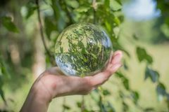 World environmental concept. Crystal globe in human hand on beautiful green and blue bokeh.  Royalty Free Stock Image