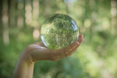 World environmental concept. Crystal globe in human hand on beautiful green and blue bokeh Royalty Free Stock Photos