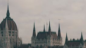 The world famous parliament building in Budapest built in the Gothic in the background of an airplane flying from above. In cloudy weather stock video