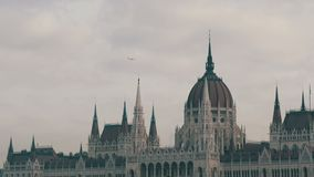 The world famous parliament building in Budapest built in the Gothic in the background of an airplane flying from above. In cloudy weather stock video footage