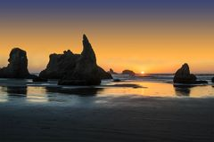 World famous Wizard`s Hat in Bandon, OR. Sun on the horizon in Bandon, OR, behind Wizard`s Hat Royalty Free Stock Image