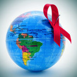 World fight against AIDS. A red awareness ribbon on a terrestrial globe depicting the idea of the world fight against AIDS Stock Photos