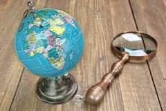 World Geographical Globe And Magnifier On The Wooden Table Royalty Free Stock Images