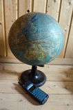 World geographical globe and retro cellphone on the wooden backg. Old sphere and retro mobile phone on the light wooden background Royalty Free Stock Photography