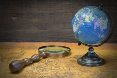World Globe  And Magnifier On The Old Map Royalty Free Stock Photos