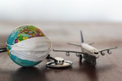 World globe with medical face mask on and medical stethoscope and airplane on wooden table. Virus, Coronavirus, Covid-19,