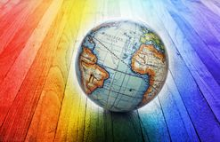 World Rainbow Globe Background. A world globe with a rainbow wood background stock images