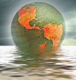 World Globe. Showing the northern and southern hemispheres over placid water Royalty Free Stock Photo