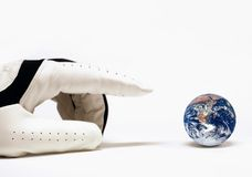 The world within grasp. Hand with golf glove trying to capture the earth. Concept for world at my finger tips. Earth image from http://visibleearth.nasa.gov Royalty Free Stock Images