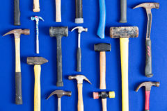 World of hammers. With a large assortment of different shapes arranged neatly in vertical lines on a bright blue background in a DIY, carpentry, building Stock Photography
