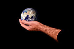World in hand. Composite image of man holding the planet earth in the palm of his hand against a black background Stock Images