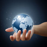 World in hand on blue background Royalty Free Stock Photography