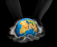 World in hands. Hands holding a gloving globe in dark Stock Photography