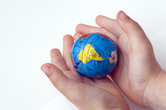 World in Hands. Small child holds world globe in his hands royalty free stock image
