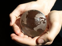 World in Hands. A child holds a glass ball of the world in their hands stock images