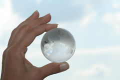World in hands. Glass globe in hand on blue sky Stock Photos