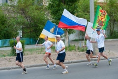 World Harmony Run. ULAN-UDE, RUSSIA - JUNE 11: Unidentified volunteers of World Harmony Run run carrying a torch, a symbol of harmony, flags of WHR, Russia Stock Image