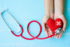 World health day, Healthcare and medical concept. Woman hand holding red heart with Stethoscope, notepad or notebook, thermometer and yellow Pill on Pastel stock image