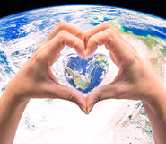World in heart shape with over women human hands on blurred natu Stock Photo