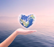 World in heart shape with over women human hands Royalty Free Stock Image