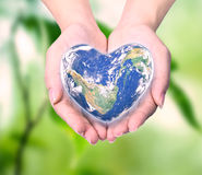 World in heart shape with over women human hands Royalty Free Stock Images