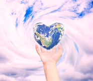 World in heart shape with over women human hands Stock Images