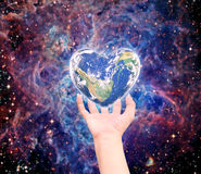 World in heart shape with over women human hands Stock Photos
