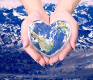 World in heart shape with over women human hands. Royalty Free Stock Images
