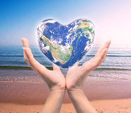 World in heart shape with over women human hands. Stock Image