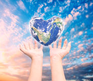 World in heart shape with over women human hands. Royalty Free Stock Photography