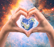 World in heart shape with over women human hands. Stock Photos