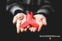 Red ribbon on palms. World hemophilia day Red ribbon on palms Royalty Free Stock Image