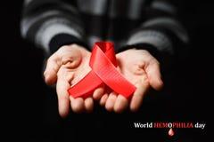 Red ribbon on palms. World hemophilia day Red ribbon on palms Stock Image