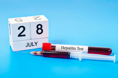 World hepatitis day concept. 28 July calendar wood and sample blood for hepatitis test. World hepatitis day concept Royalty Free Stock Photography