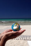 World in her hands. A woman with her hands open holding the world on the beach Royalty Free Stock Image
