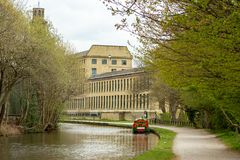 Canal boat approaches Saltaire stock photography