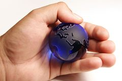 The world in his hands. A man's hand holding a glass globe representing the world royalty free stock photography