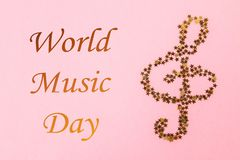 World, international music day. Musical notes of starry golden confetti lying on a pink pastel background. World, international music day. Musical notes of stock images
