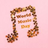 World, international music day. Musical notes of starry golden confetti lying on a pink pastel background. World, international music day. Musical notes of royalty free stock images
