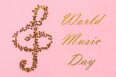 World, international music day. Musical notes of starry golden confetti lying on a pink pastel background. World, international music day. Musical notes of royalty free stock photography