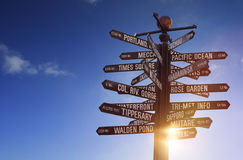 World Landmarks Signpost glowing sun, blue sky and free copy space. World Landmarks Signpost with many different signs, airplane, glowing sun and sky during Stock Images
