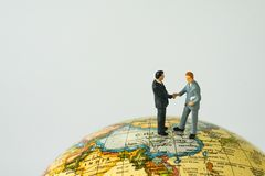 World leaders agreement hand shake teamwork concept with miniatu. Re business leaders hand shaking standing on globe map with copy space white background Royalty Free Stock Photo