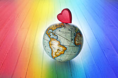 World Love Rainbow Heart Background. A red heart on a world globe with a rainbow background royalty free stock images