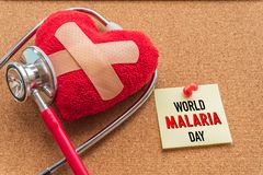 World MALARIA day April 25, Healthcare and medical concept. Stethoscope, handmade red heart, thermometer and yellow Pill on blue Pastel wooden table background Stock Images