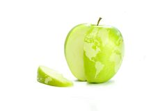 World Map on Apple. World map on a fresh green apple with a slice cut out symbolizing concepts of trade, world hunger, poverty, globalization Stock Images