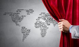 World map behind drapery curtain and hand opening it stock photo