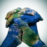 World map in the clasped hands of a man (Earth map furnished by Royalty Free Stock Photography