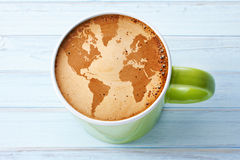 World Coffee Cup Fair Trade Background. A cappuccino in a green cup with a world map created in the foam on a blue background royalty free stock images