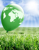 World map environmental scene. Green balloon with world map over field of grass Royalty Free Stock Photos